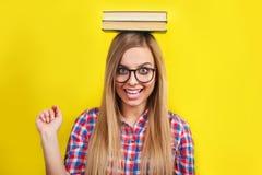 Mujer joven en los vidrios que sostienen los libros en su cabeza El estudiante elegante joven sonriente se está colocando con los Fotos de archivo libres de regalías
