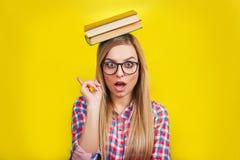 Mujer joven en los vidrios que sostienen los libros en su cabeza El estudiante elegante joven sonriente se está colocando con los Imagen de archivo