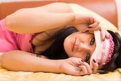 Mujer joven en máscara de ojo del sueño Imagenes de archivo