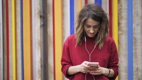 Mujer joven en mandar un SMS rojo y escuchar la música cerca de una pared colorida, cierre para arriba metrajes
