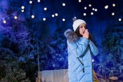 Mujer joven en manos que se calientan y la situación abajo de la chaqueta azul cerca Fotos de archivo