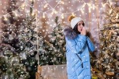 Mujer joven en manos que se calientan y la situación abajo de la chaqueta azul cerca Foto de archivo libre de regalías