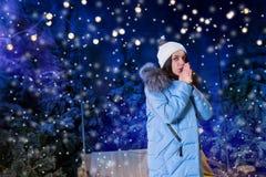 Mujer joven en manos que se calientan y la situación abajo de la chaqueta azul cerca Fotografía de archivo libre de regalías