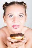 Mujer joven en maquillaje brillante que come un buñuelo sabroso con la formación de hielo Mujer alegre divertida con los dulces,  Imagenes de archivo