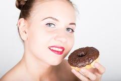 Mujer joven en maquillaje brillante que come un buñuelo sabroso con la formación de hielo Mujer alegre divertida con los dulces,  Fotografía de archivo