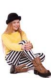 Mujer joven en pantalones rayados y sombrero negro Fotografía de archivo