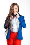 Mujer joven en pantalones rojos y capa azul que sonríe en cámara Fotos de archivo