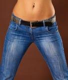 Mujer joven en pantalones vaqueros - vientre y caderas del primer Fotografía de archivo