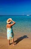 Mujer joven en pareo y sombrero que mira el SE Imagen de archivo libre de regalías