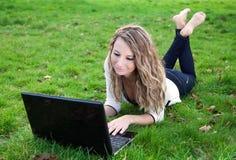 Mujer joven en parque con la computadora portátil Imágenes de archivo libres de regalías