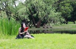 Mujer joven en parque, libro y la lectura verdes Felicidad, hermosa fotos de archivo