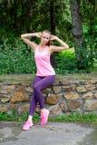 Mujer joven en paseo del estilo sport del deporte en parque de la ciudad en el día soleado después de entrenar Concepto de forma  Imagenes de archivo