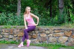 Mujer joven en paseo del estilo sport del deporte en parque de la ciudad en el día soleado después de entrenar Concepto de forma  Imagen de archivo
