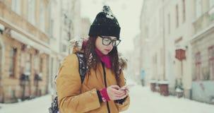 Mujer joven en paseos de moda del equipo en la ciudad del invierno que pasa por los cafés locales, textos vía su teléfono, hojean metrajes