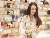 Mujer joven en perfumería imagenes de archivo