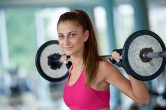 Mujer joven en pesos de elevación del gimnasio de la aptitud Imagen de archivo
