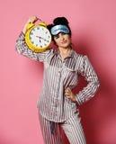 Mujer joven en pijama enseguida después que el sueño despertó con el despertador amarillo del vendaje del control soñoliento de l fotografía de archivo libre de regalías