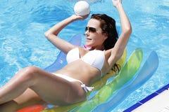 Mujer joven en piscina en un colchón Imágenes de archivo libres de regalías