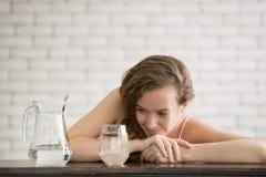 Mujer joven en posturas alegres con el jarro y el vidrio de agua potable fotos de archivo libres de regalías