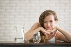 Mujer joven en posturas alegres con el jarro y el vidrio de agua potable fotografía de archivo