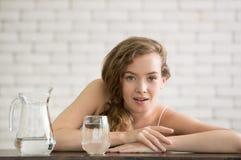 Mujer joven en posturas alegres con el jarro y el vidrio de agua potable fotos de archivo