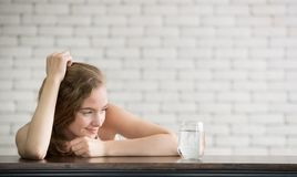 Mujer joven en posturas alegres con el jarro y el vidrio de agua potable imagen de archivo libre de regalías