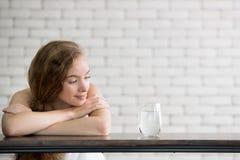 Mujer joven en posturas alegres con el jarro y el vidrio de agua potable foto de archivo