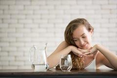 Mujer joven en posturas alegres con el jarro y el vidrio de agua potable imagen de archivo