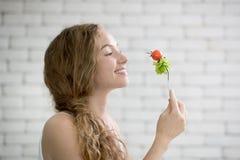 Mujer joven en posturas alegres con la mano que sostiene la ensalada en la gente imagen de archivo libre de regalías