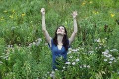 Mujer joven en prado con los brazos outstretched Fotos de archivo libres de regalías