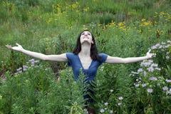 Mujer joven en prado con los brazos outstretched Imagen de archivo libre de regalías