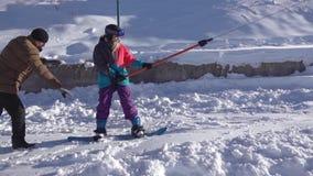 Mujer joven en remolque de cuerda de cogida de la snowboard en la cuesta del esquí almacen de metraje de vídeo