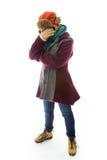 Mujer joven en ropa caliente y el recubrimiento de su cara con su mano Foto de archivo libre de regalías