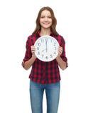 Mujer joven en ropa casual con el reloj de pared Imágenes de archivo libres de regalías