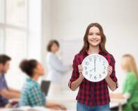 Mujer joven en ropa casual con el reloj de pared Fotografía de archivo