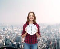 Mujer joven en ropa casual con el reloj de pared Foto de archivo libre de regalías