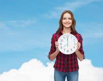 Mujer joven en ropa casual con el reloj de pared Imagen de archivo libre de regalías