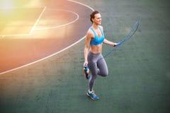 Mujer joven en ropa de deportes que ejercita con la cuerda que salta en estadio Foto de archivo libre de regalías