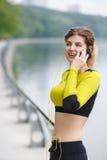 Mujer joven en ropa de deportes que habla en el teléfono móvil Fotos de archivo libres de regalías