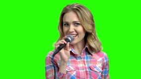 Mujer joven en ropa de sport que canta en micrófono almacen de metraje de vídeo