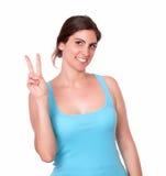 Mujer joven en ropa del gimnasio que gesticula la muestra de la victoria Imagen de archivo