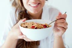 Mujer joven en ropa interior que come los cereales Aislado en blanco Foto de archivo
