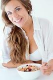 Mujer joven en ropa interior que come los cereales Aislado en blanco Imágenes de archivo libres de regalías