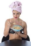 Mujer joven en ropa interior que come los cereales de desayuno después de ducha Imágenes de archivo libres de regalías