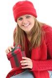 Mujer joven en ropa roja del invierno con el rectángulo de regalo Foto de archivo