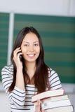 Mujer joven en sala de clase usando el teléfono móvil Fotografía de archivo