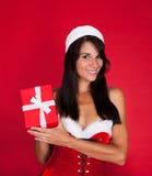 Mujer joven en Santa Claus Costume Holding Present Fotos de archivo