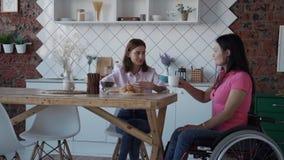 Mujer joven en silla de ruedas que habla con su amigo en casa metrajes