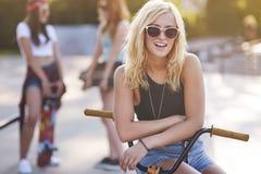 Mujer joven en skatepark con sus amigos Imagen de archivo libre de regalías
