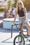 Mujer joven en skatepark con sus amigos Fotos de archivo